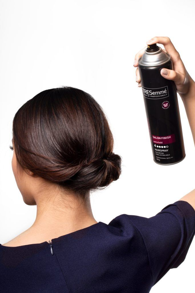 Chignon for short hair: Back shot of Asian woman spraying hairspray on her dark hair in chignon
