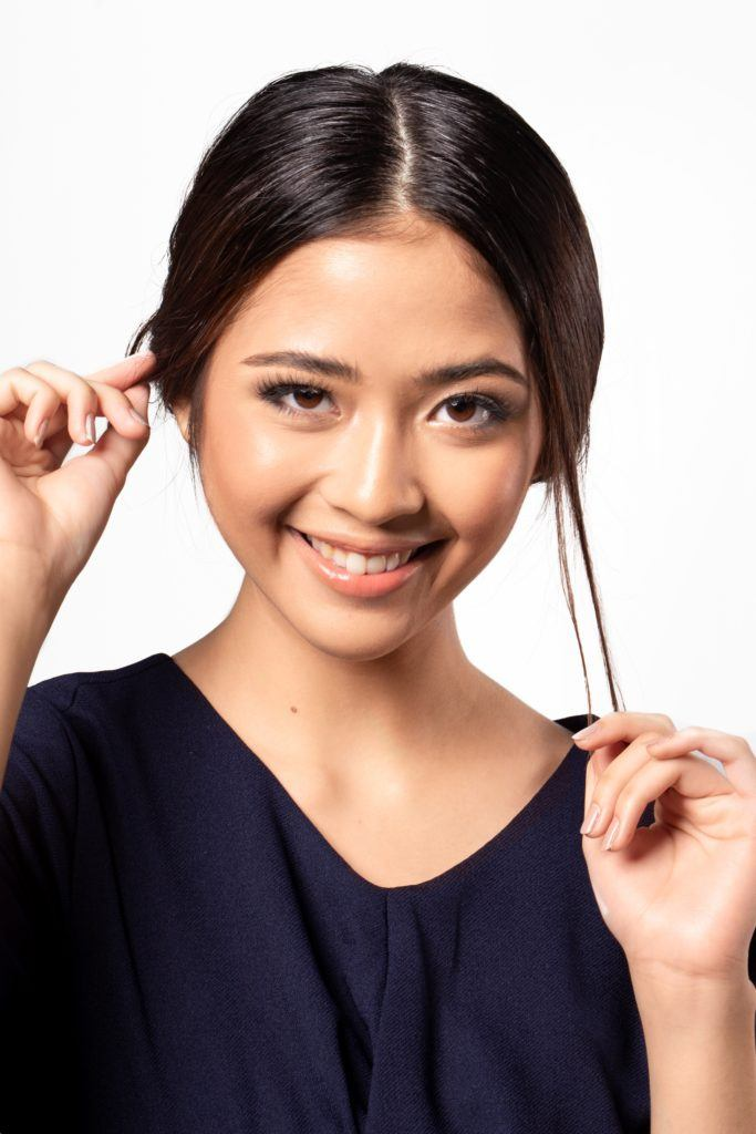 Chignon for short hair: Closeup shot of an Asian woman with dark hair loosening hair strands