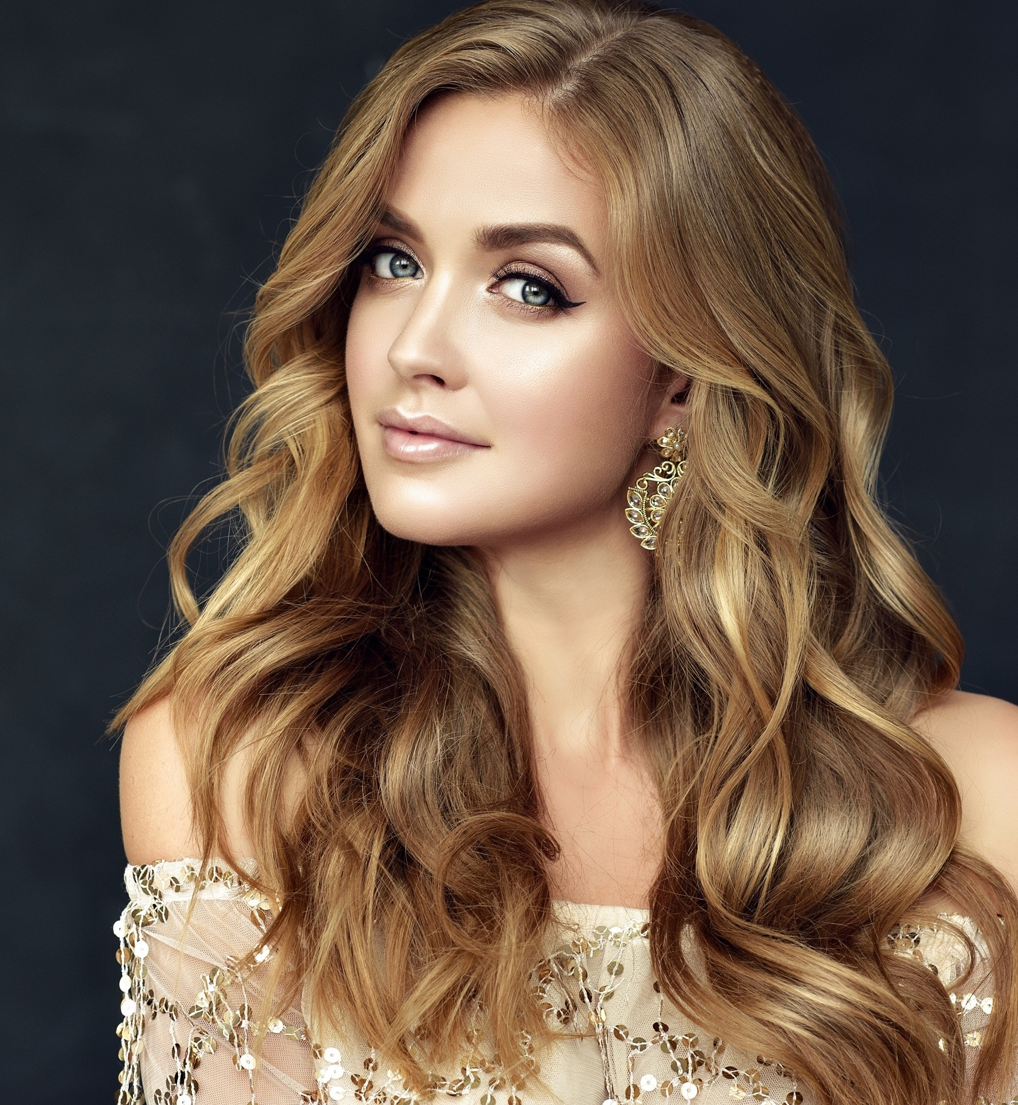 Golden brown hair color: Closeup shot of a woman with long brown wavy hair against a dark backdrop