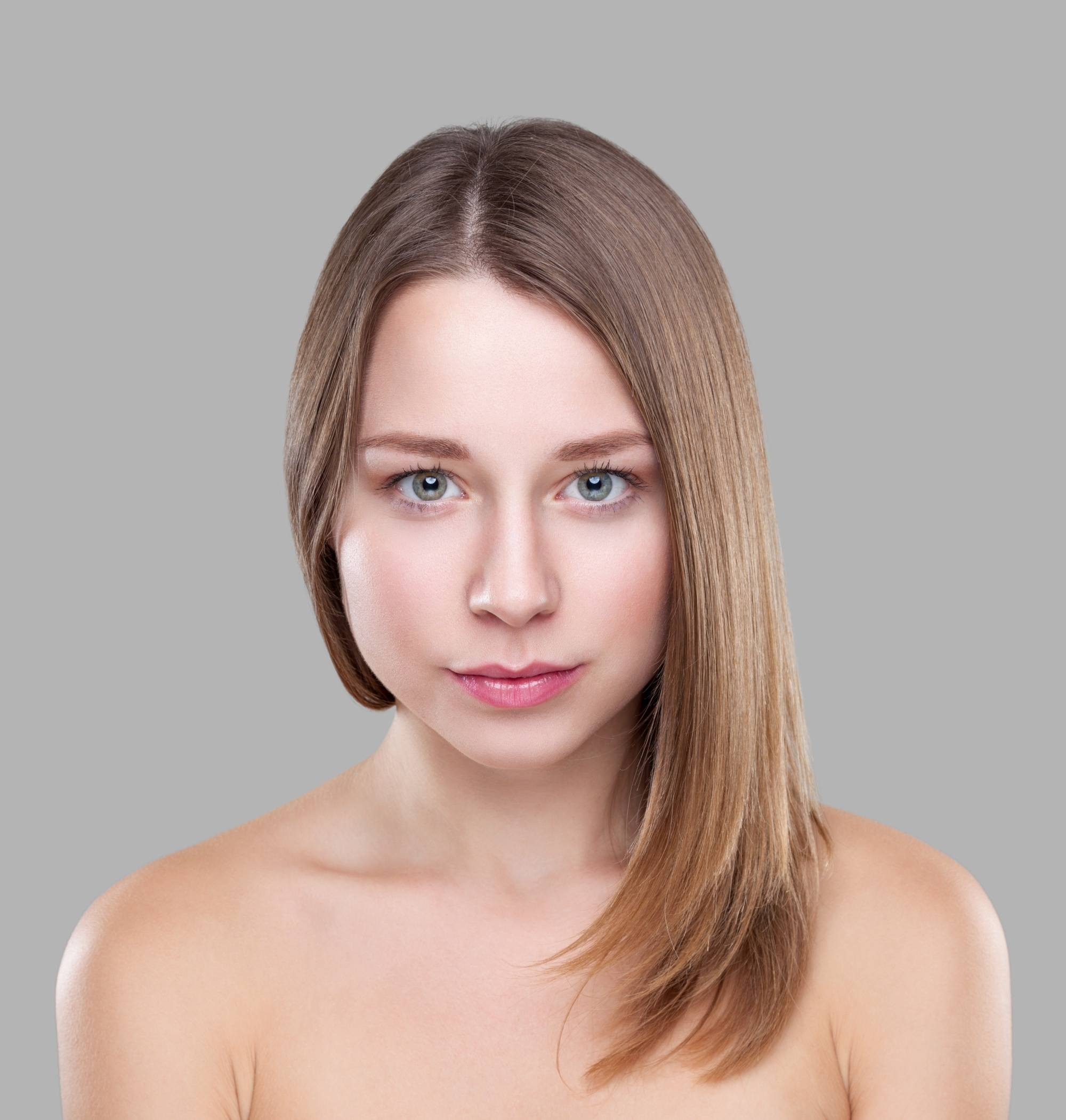 Golden brown hair color: Closeup shot of a woman with straight brown hair against a gray backdrop