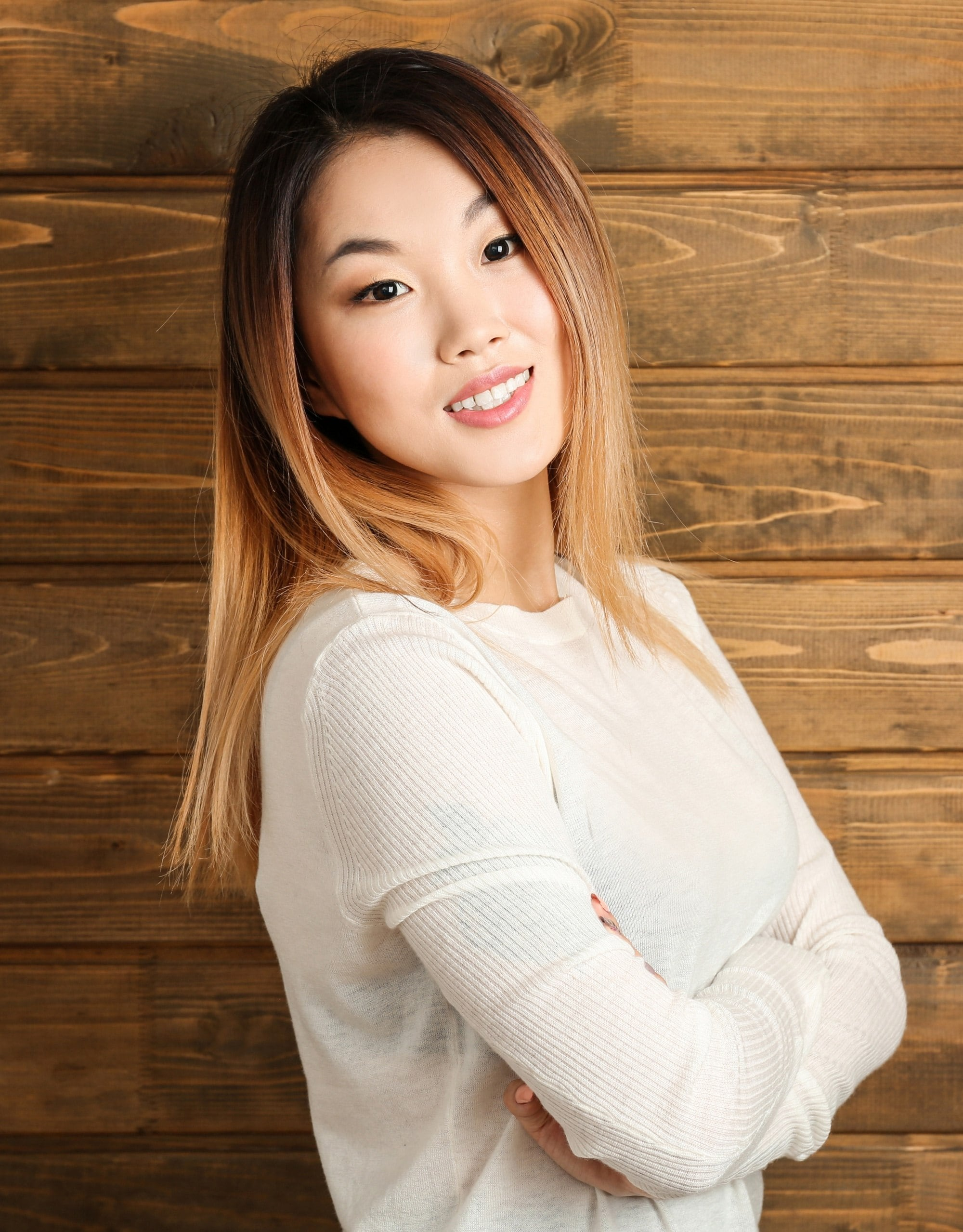 Golden brown hair color: Asian woman with long straight brown ombre hair wearing a white sweater against a wooden backdrop