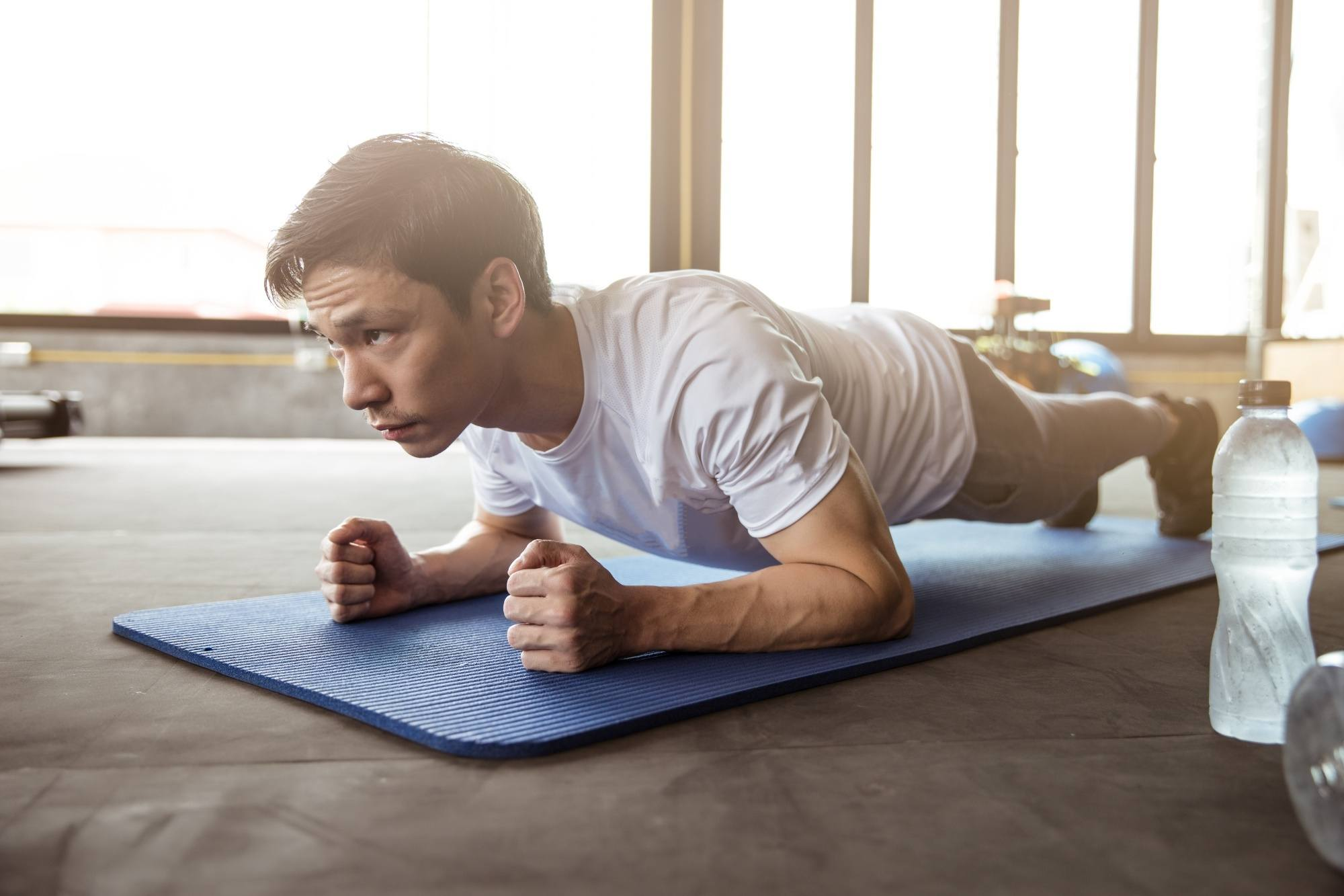 Hair care tips for men: Man doing planks on a mat on the floor