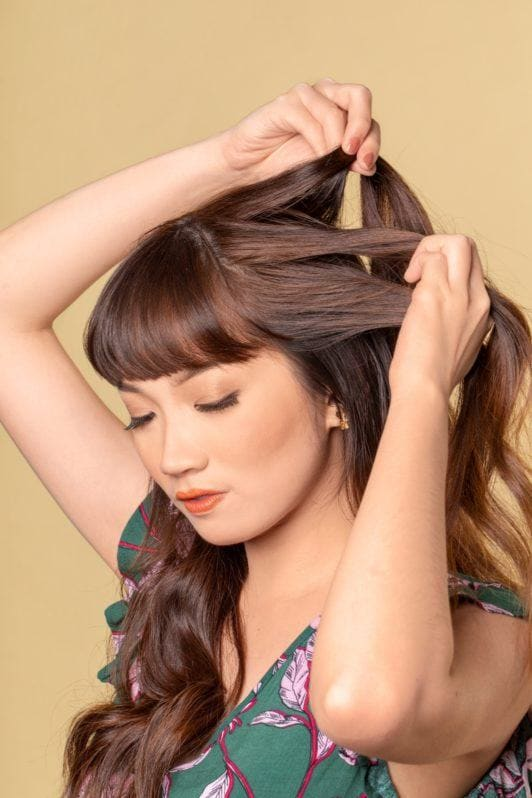 Half up boho braid: Asian woman holding sections of her long dark brown hair with bangs