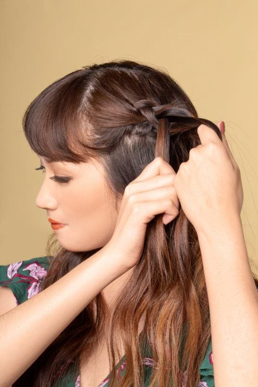 Half up boho braid: Closeup of an Asian woman braiding a section of her long dark brown hair with bangs