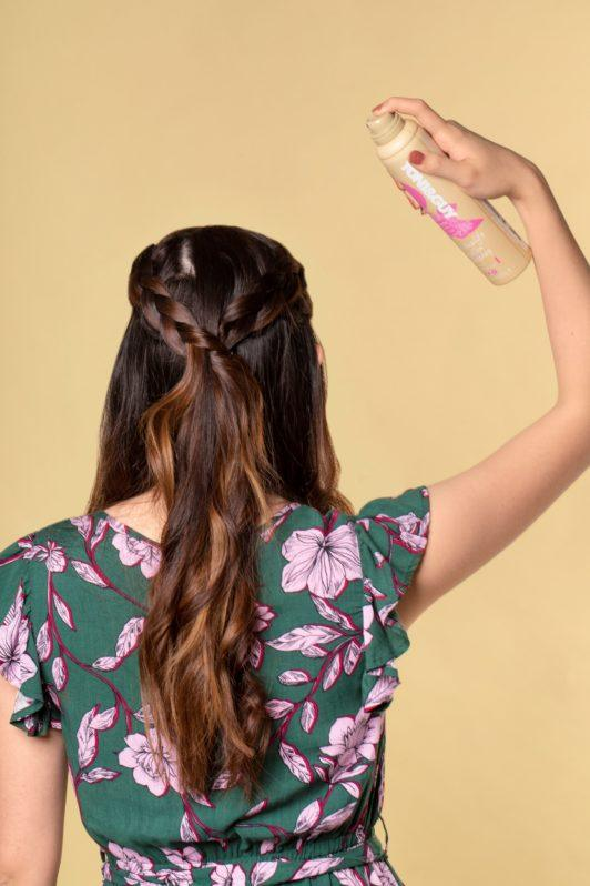 Half up boho braid: Back shot of an Asian woman spraying hairspray on her dark brown braided hair