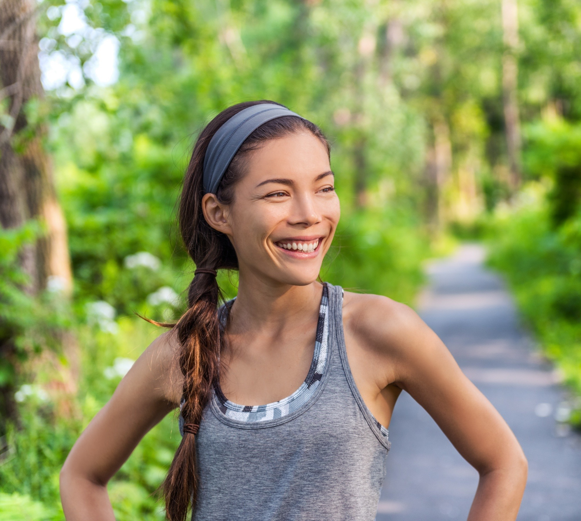 Headband hairstyles: Asian woman with long brown braided hair wearing a gray headband and gray workout top outdoors