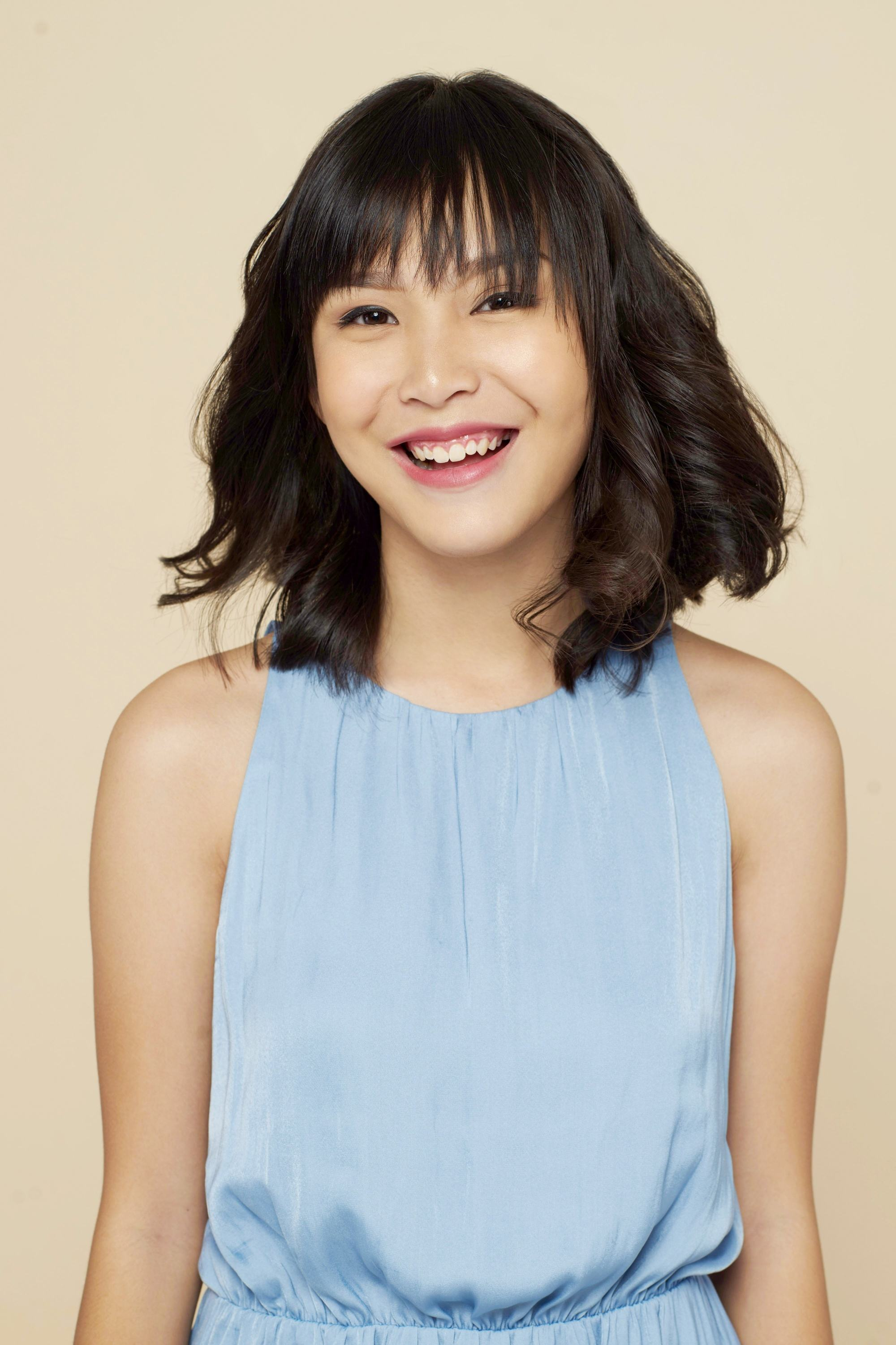 Asian woman with short black wavy hair with bangs wearing a blue sleeveless dress