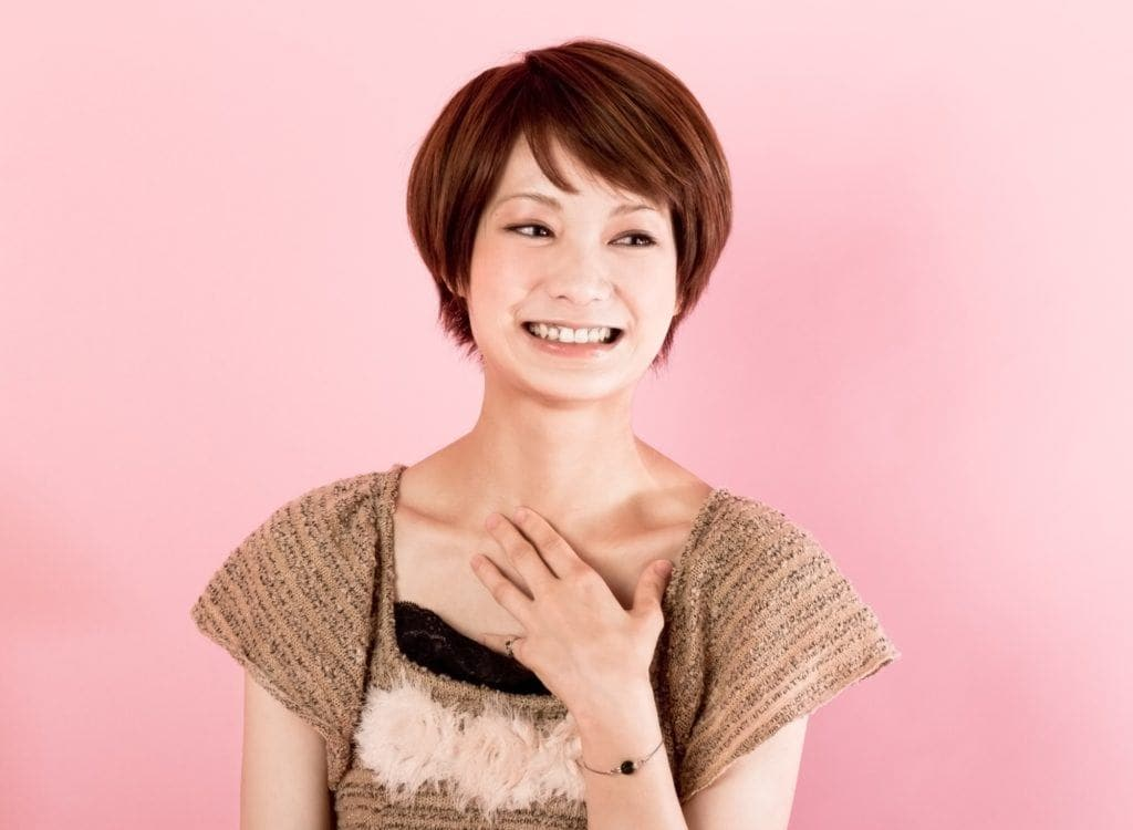 Layered short hair: Asian woman with short brown hair wearing a brown blouse smiling