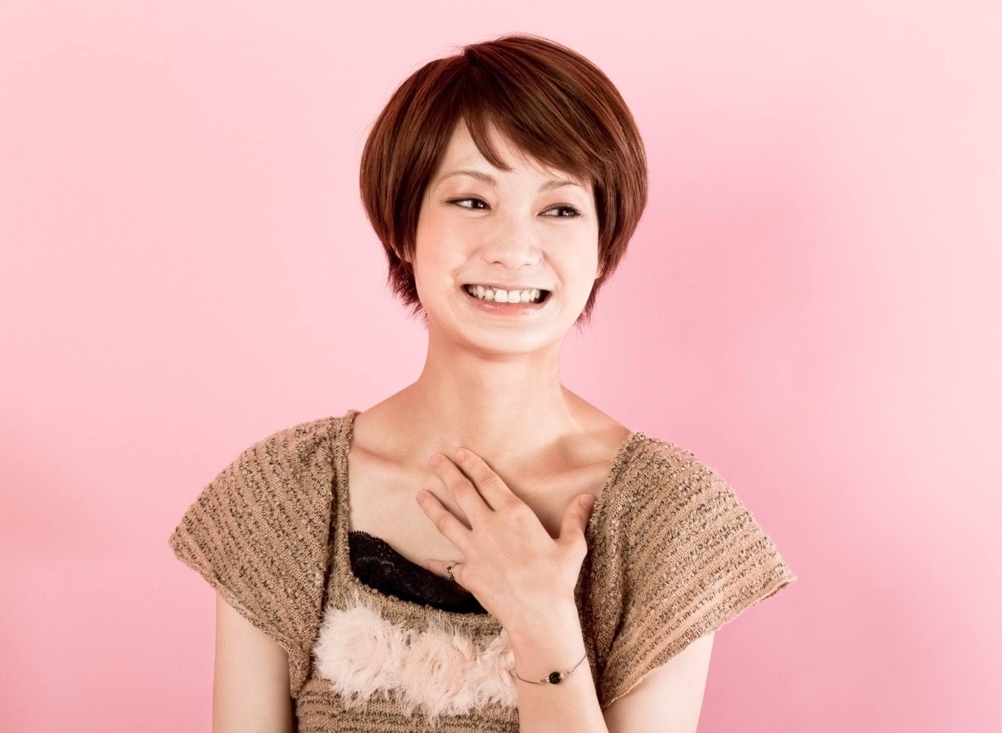 Asian woman with short brown hair wearing a brown blouse smiling