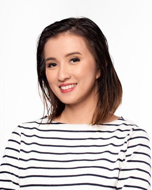 Messy layered bob: Asian woman with short dark hair wearing a striped shirt