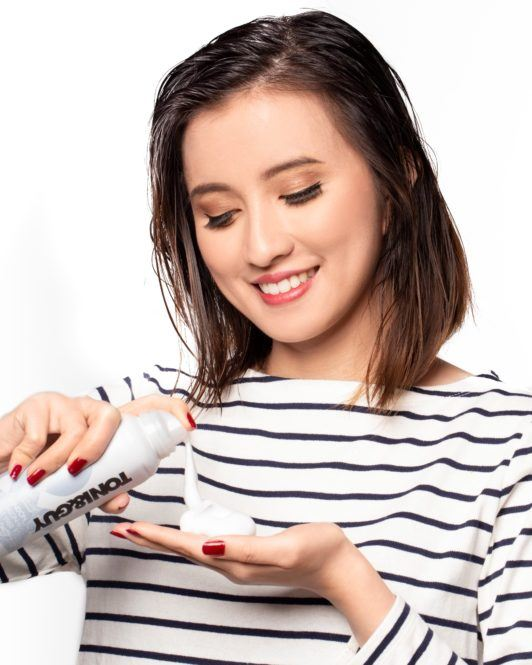Messy layered bob: Asian woman with short dark brown hair putting hair mousse on her palms
