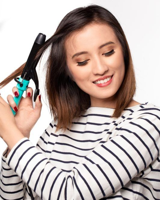 Messy layered bob: Asian woman curling her short dark brown hair and smiling