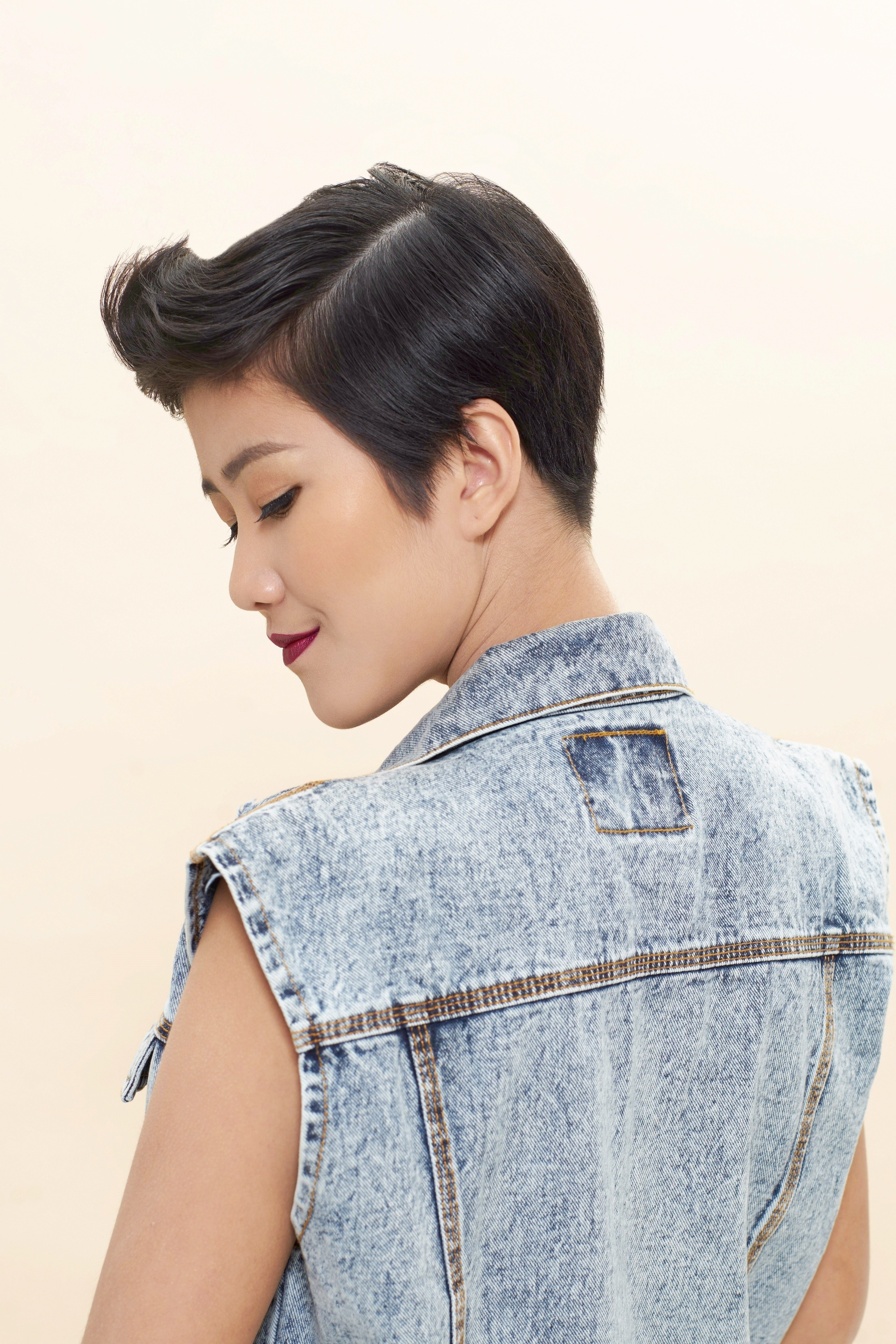 Asian woman with pixie cut with quiff wearing a sleeveless denim vest