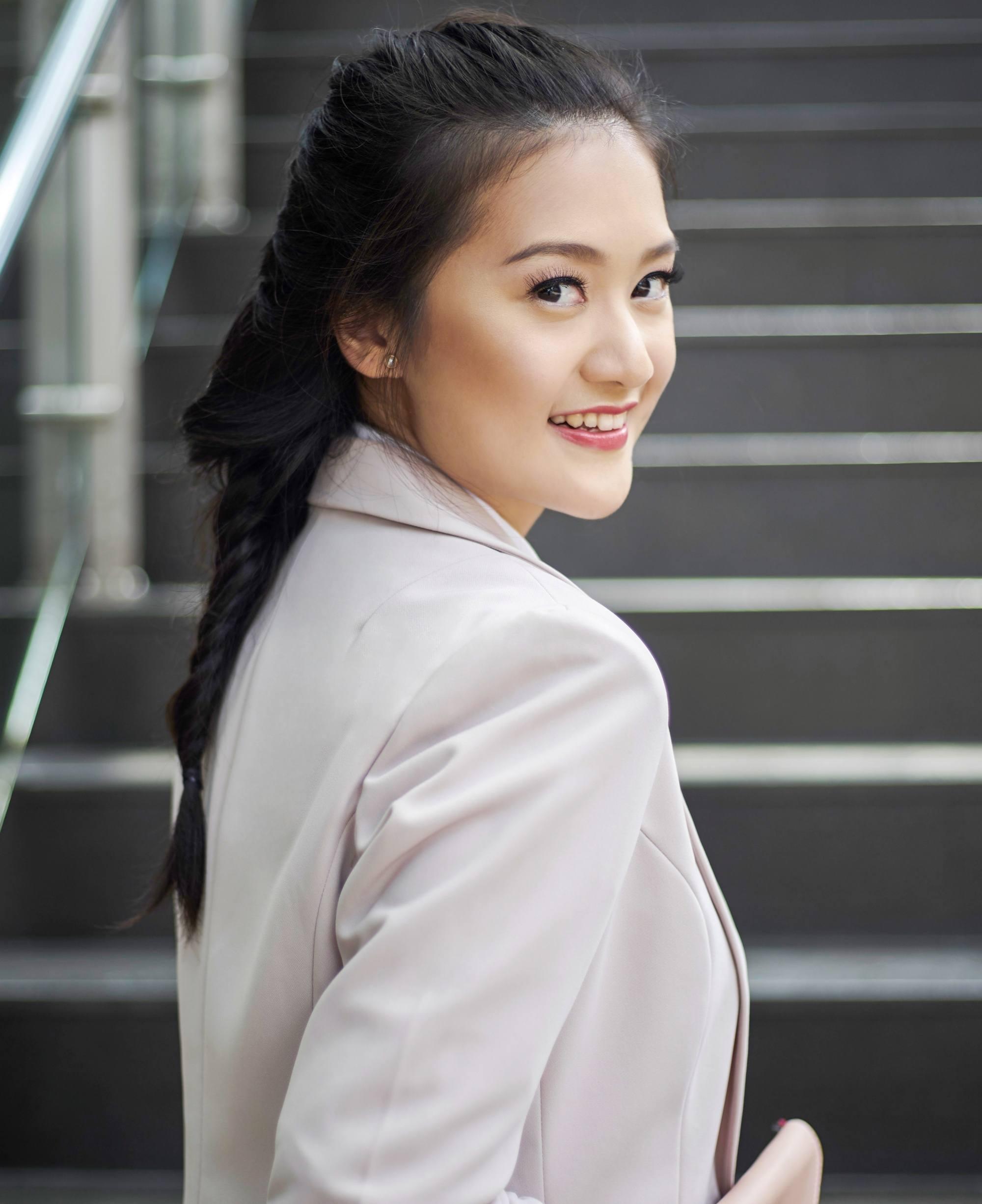 Summer braids: Asian woman with long black hair in a braid wearing a cream blazer