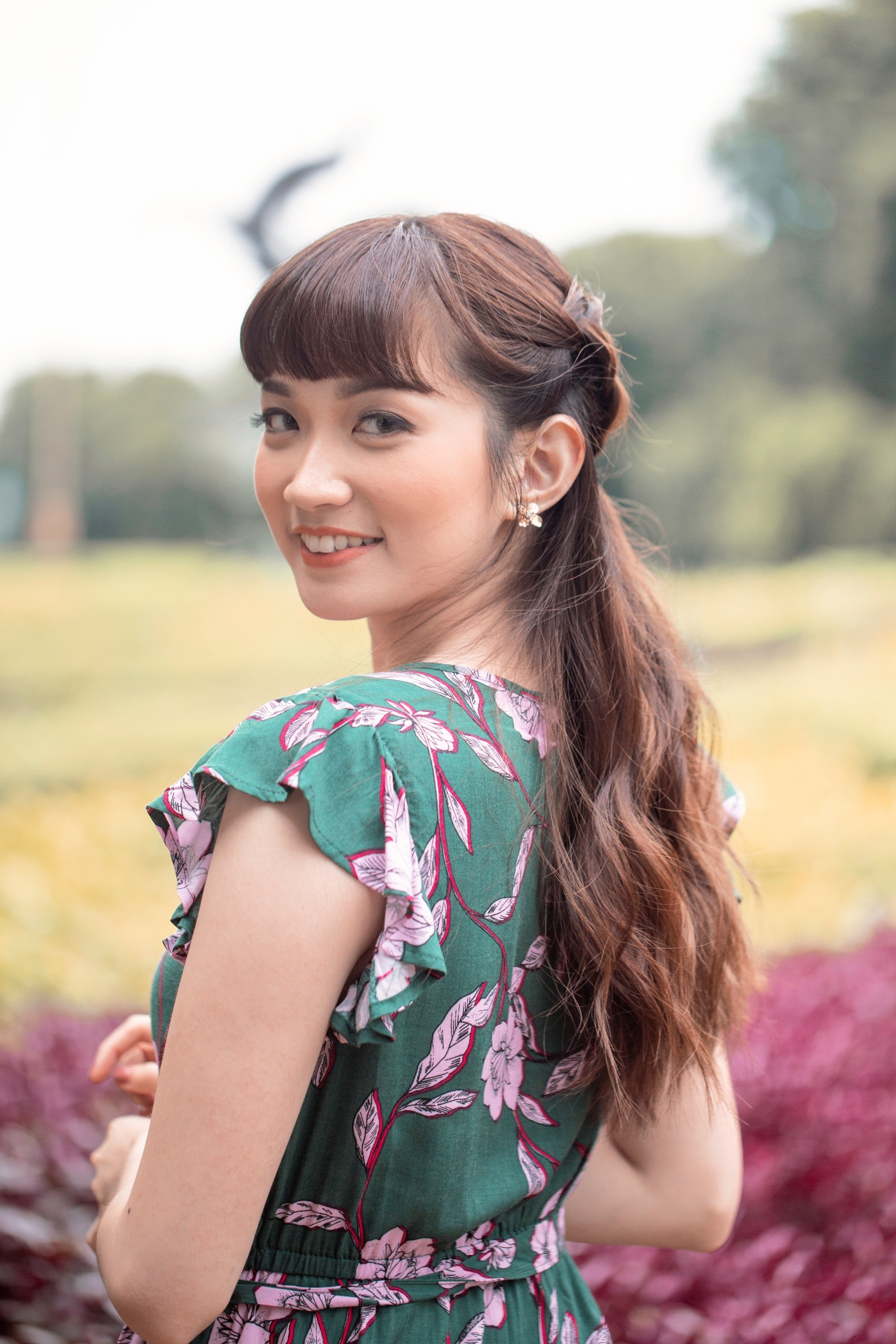 Summer braids: Asian woman with long wavy hair in a half up braid wearing a printed dress outdoors