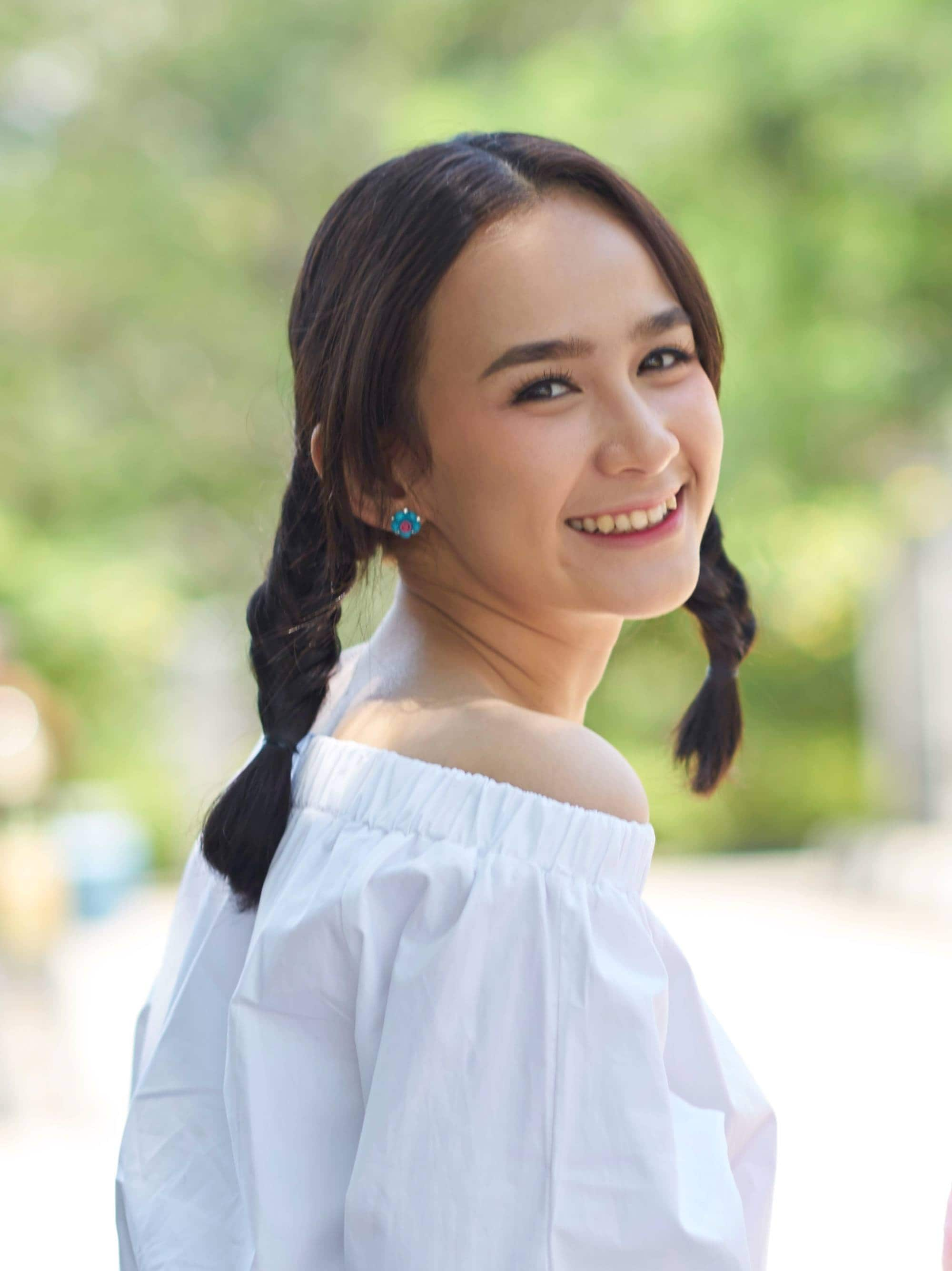 Summer braid: Closeup shot of an Asian woman with medium-length dark hair in two braids smiling outdoors