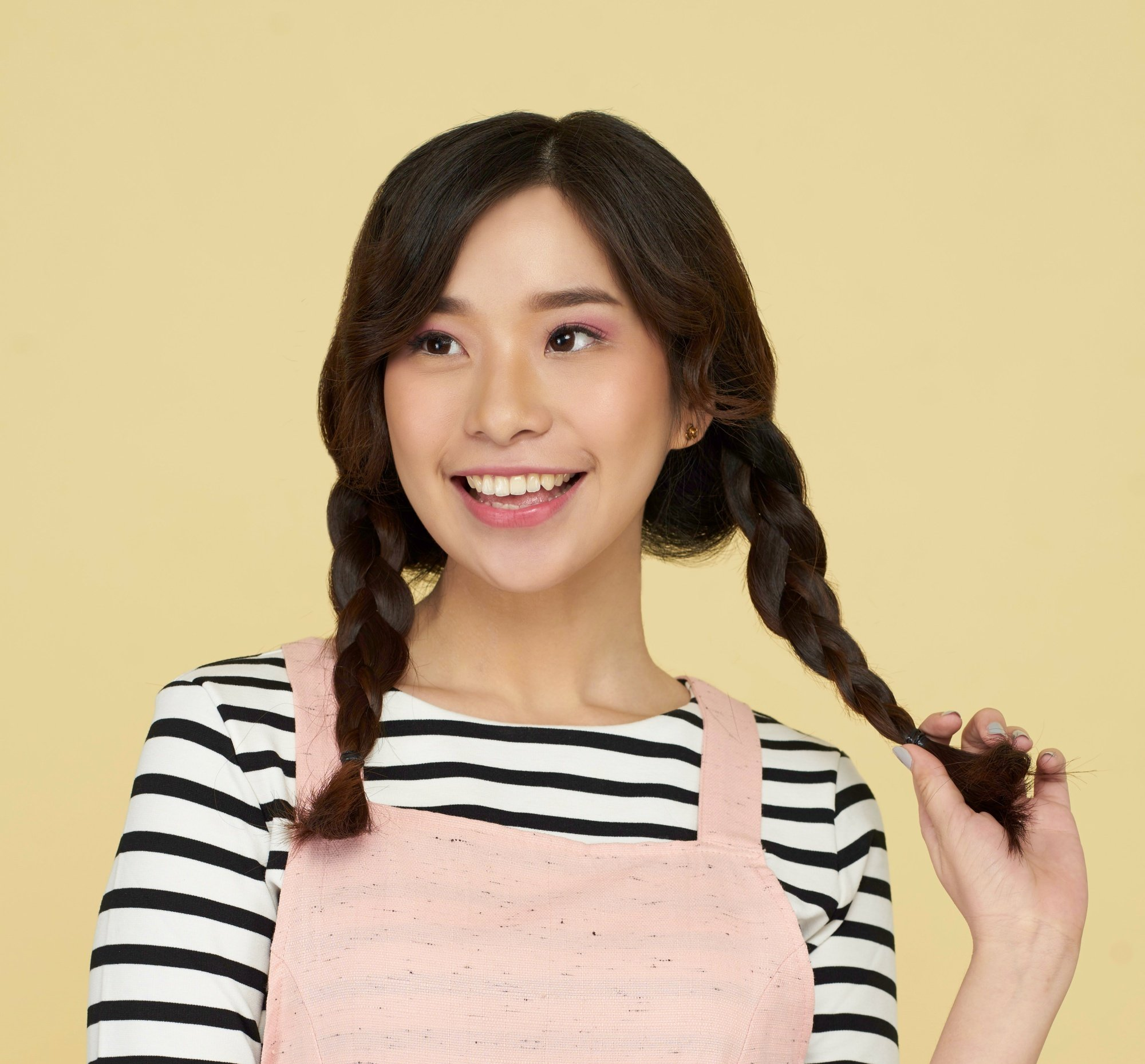 Summer braids: Closeup shot of an Asian woman with long dark brown hair in two braids wearing a striped shirt