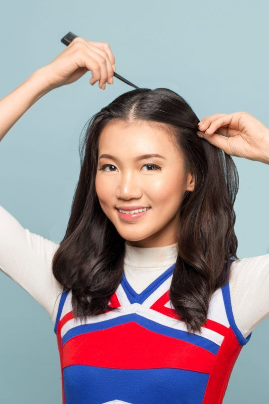 Double braided ponytail: Asian woman parting her hair with a comb
