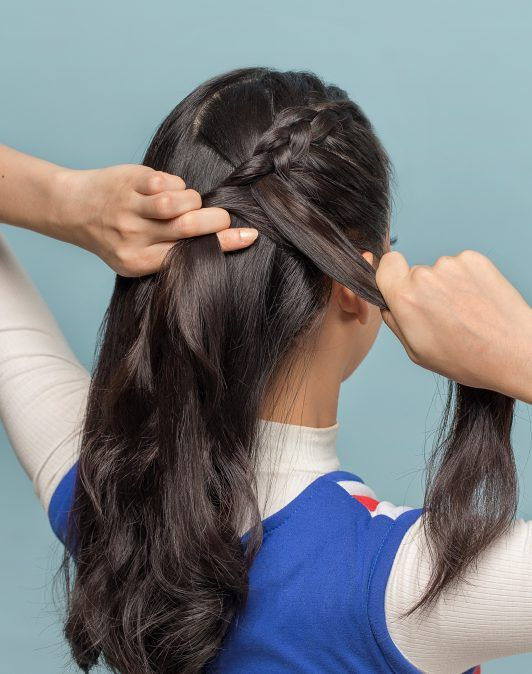 Double braided ponytail: Back shot of an Asian woman braiding her hair