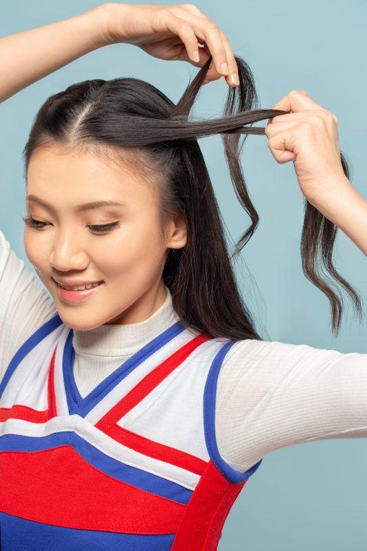 Double braided ponytail: Asian woman braiding a section of her hair