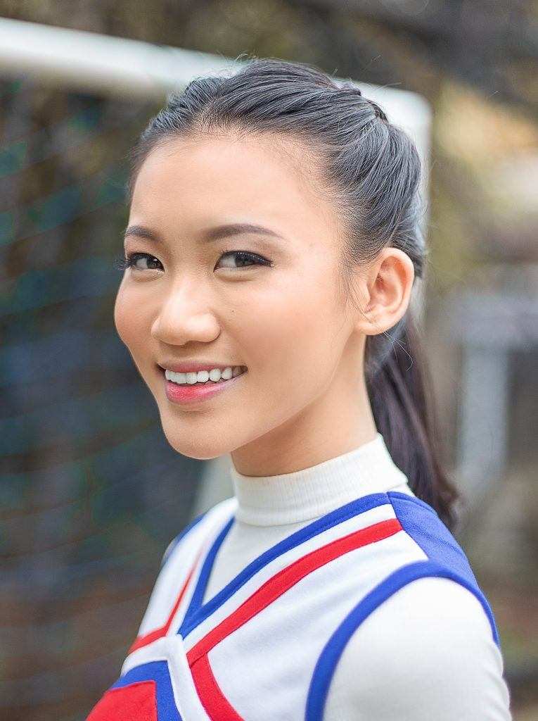 Double braided ponytail: Closeup shot of an Asian woman smiling outdoors