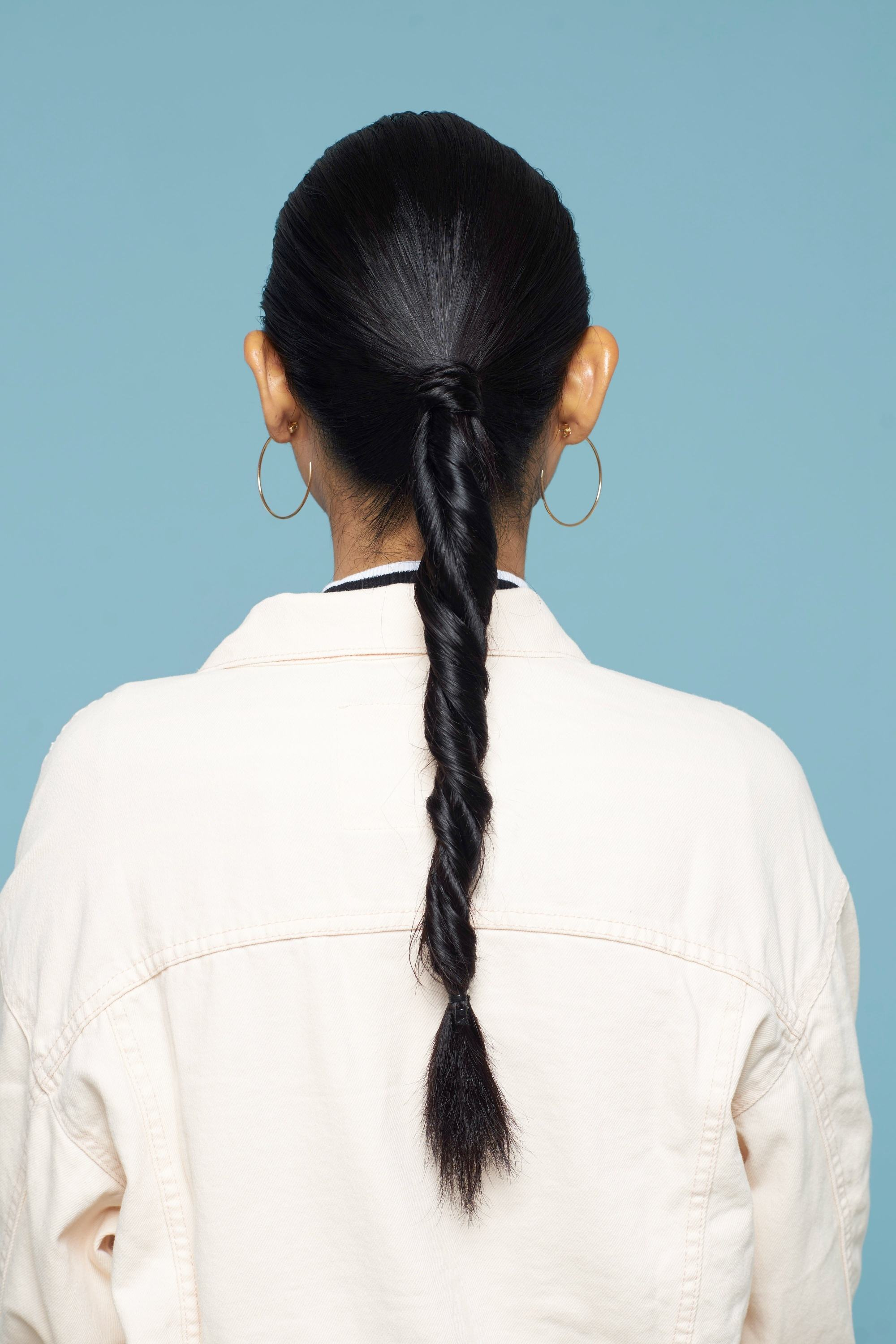 Back shot of an Asian woman with long black hair in double rope braid ponytail