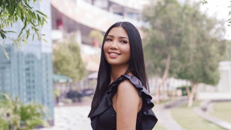 Hair facts: Asian woman with long straight black hair smiling outdoors