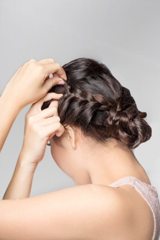 Lace braid updo: Side view of an Asian woman widening her braided updo