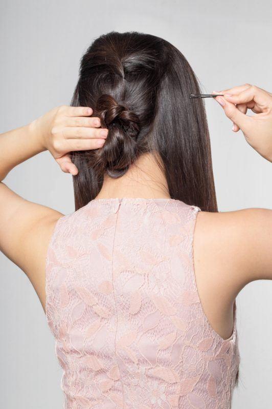 Lace braid updo: Back shot of an Asian woman creating a low hair bun