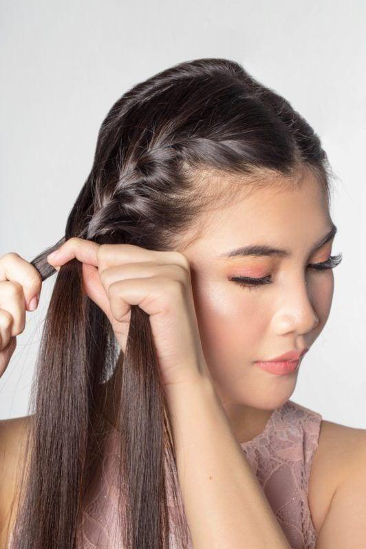 Lace braid updo: Closeup shot of an Asian woman braiding her hair