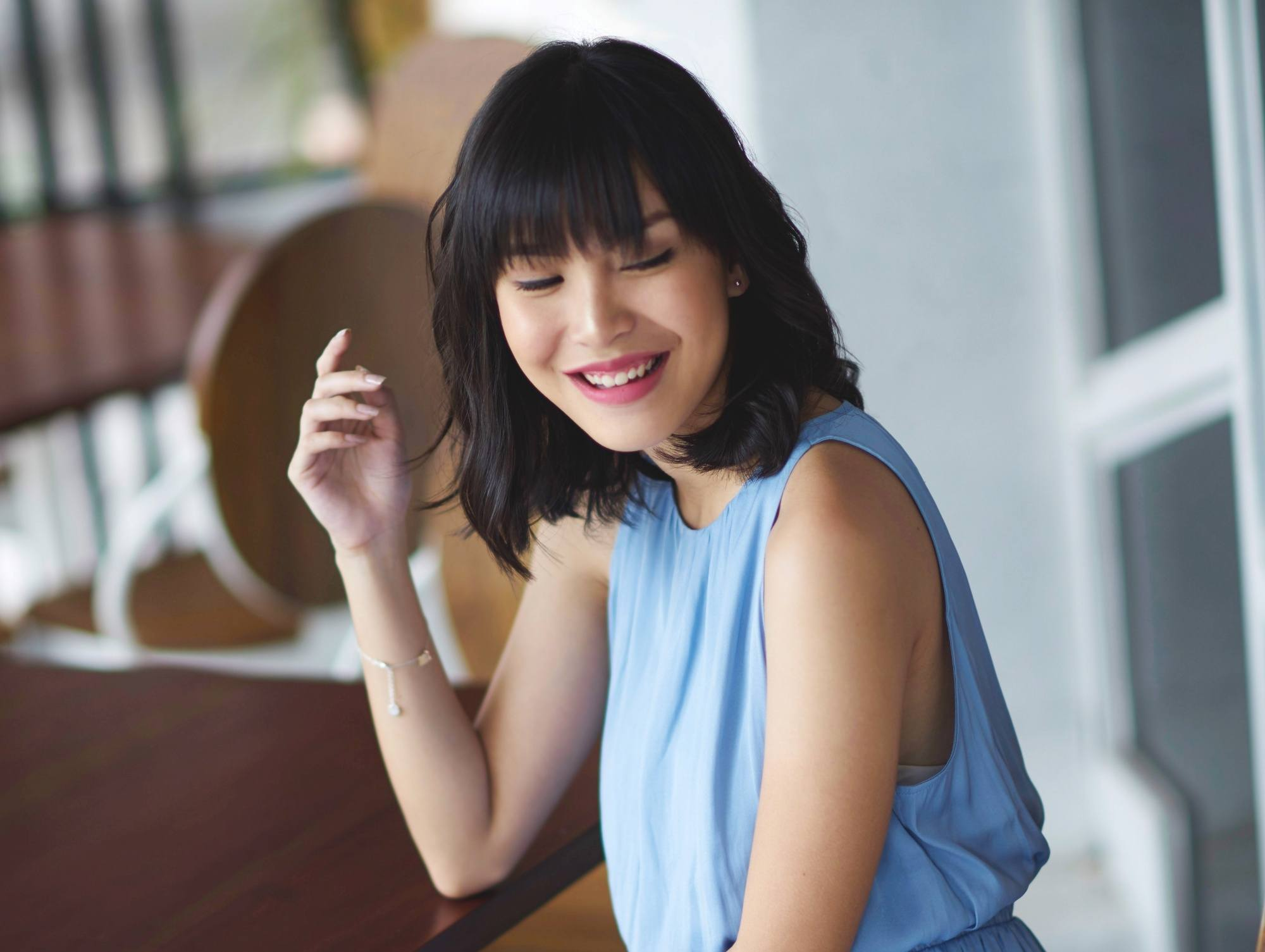 Long layered bob: Asian woman with wavy black lob with bangs smiling