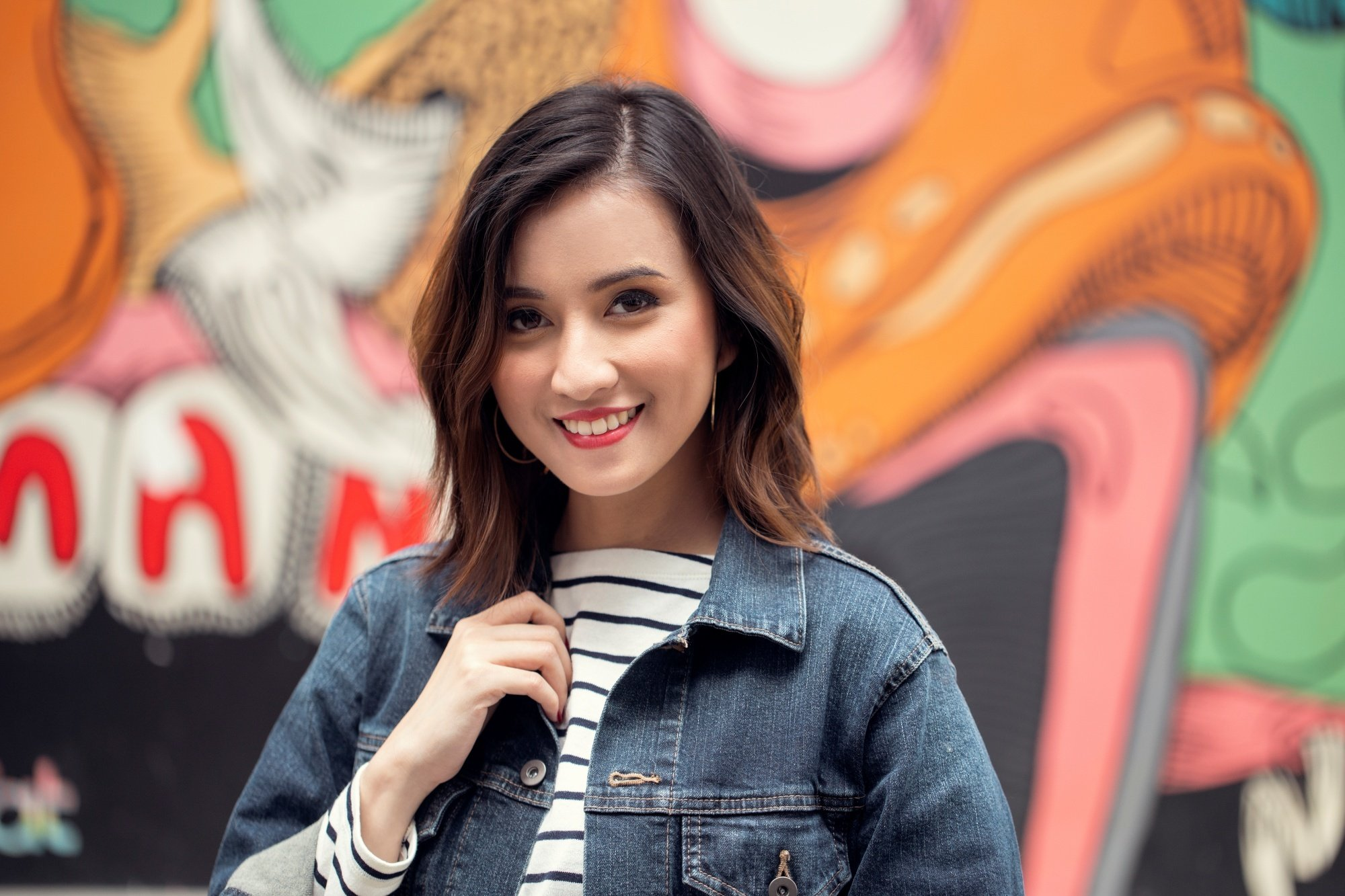Long layered bob: Asian woman with messy layered bob wearing a denim jacket against a mural