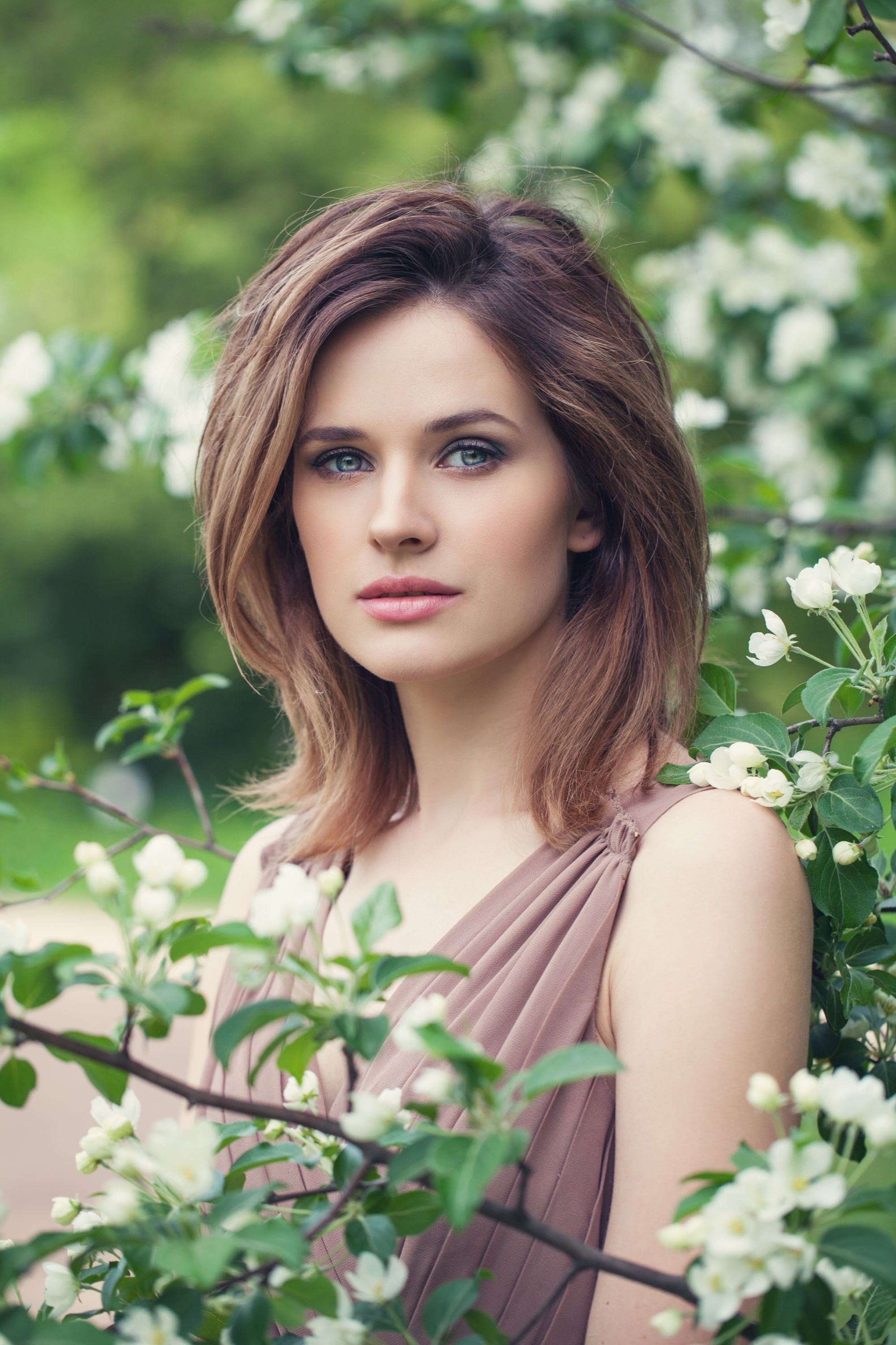 Long layered bob: Caucasian woman with brown hair surrounded by plants