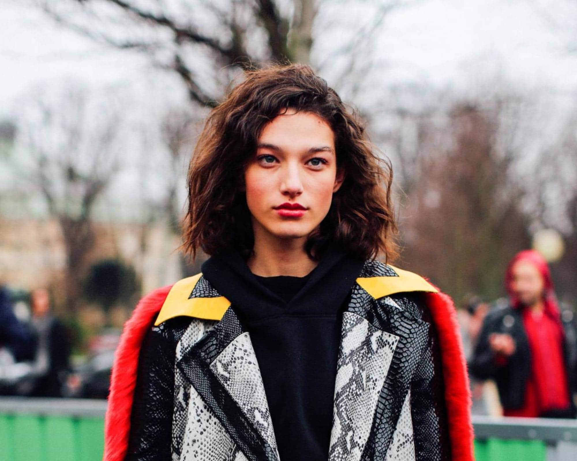 Mahogany Hair Color: Woman with short curly dark hair wearing a jacket outdoors