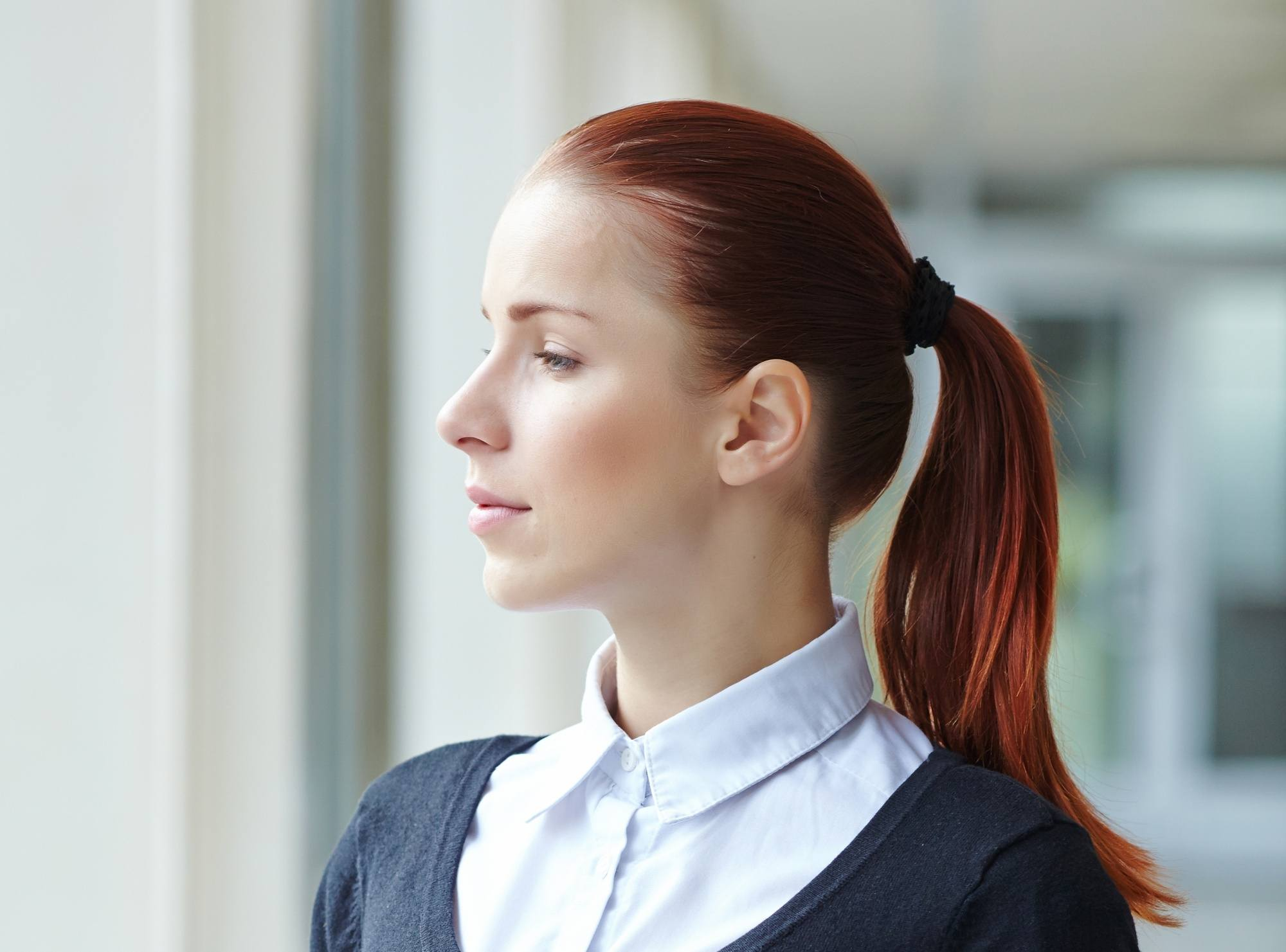Mahogany hair color: Closeup shot of a woman with long dark hair in a ponytail