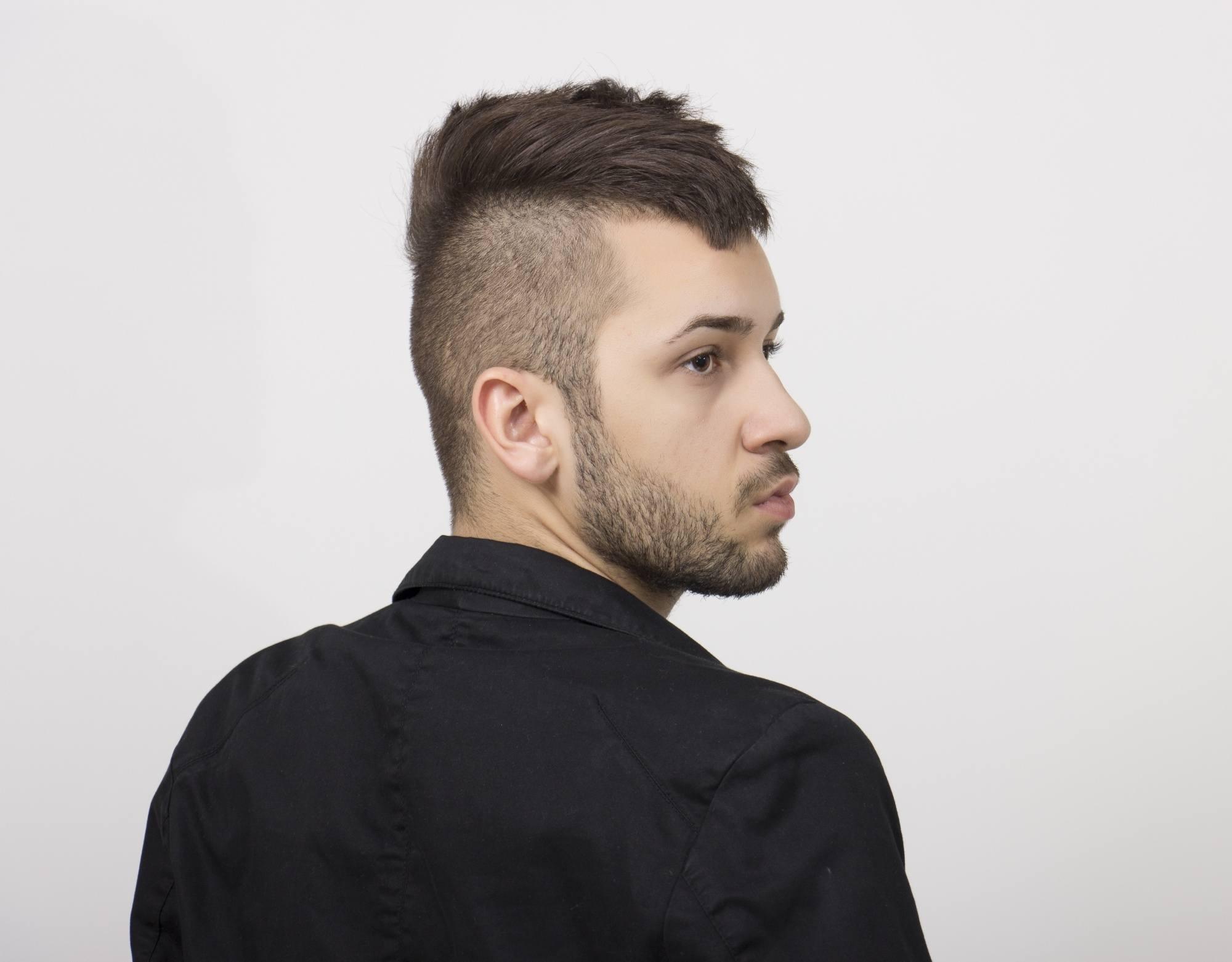Mohawk fade: Man with mohawk fade dark hair wearing a dark jacket
