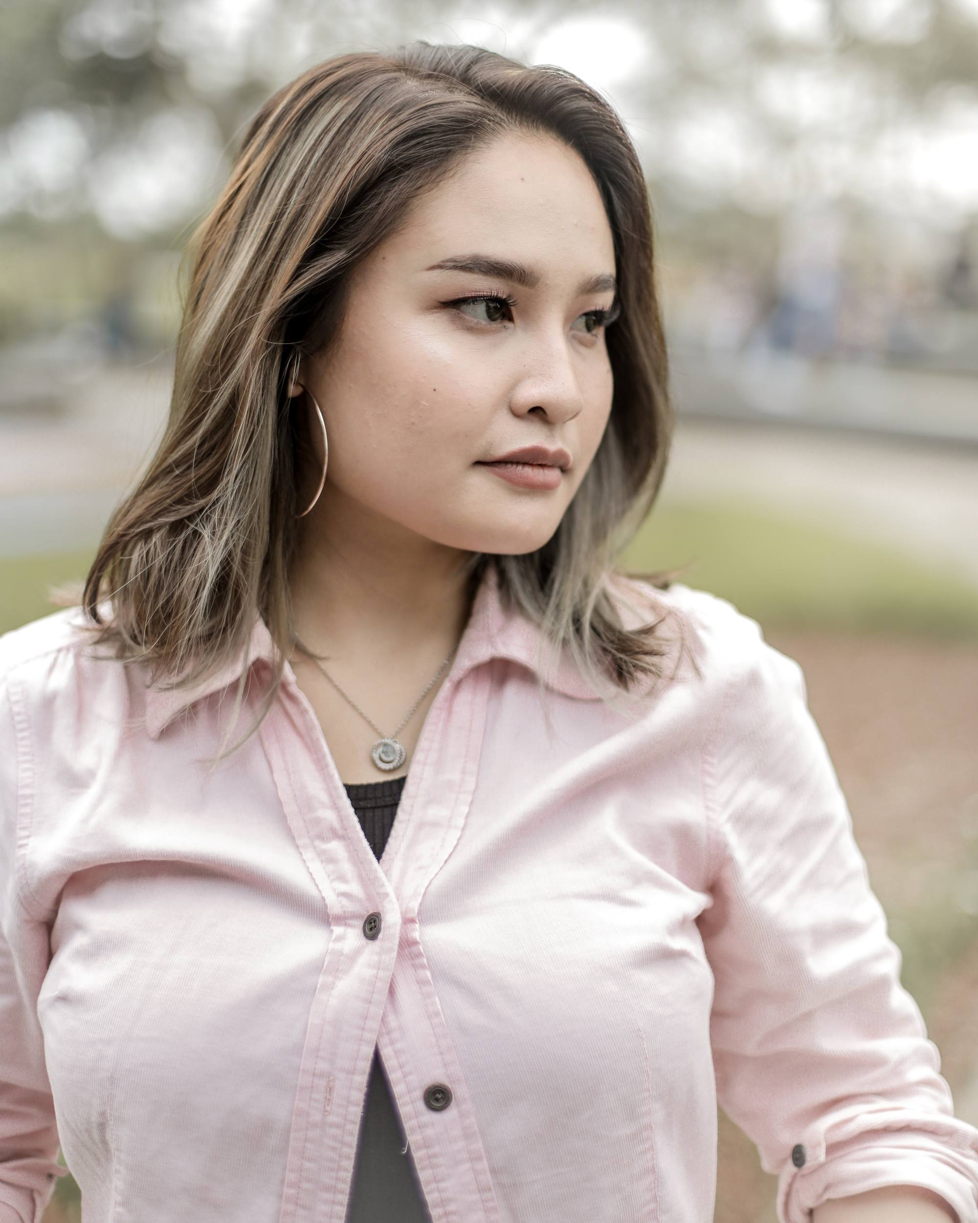 Asian woman with ash brown medium length hair wearing a pink blouse outdoors