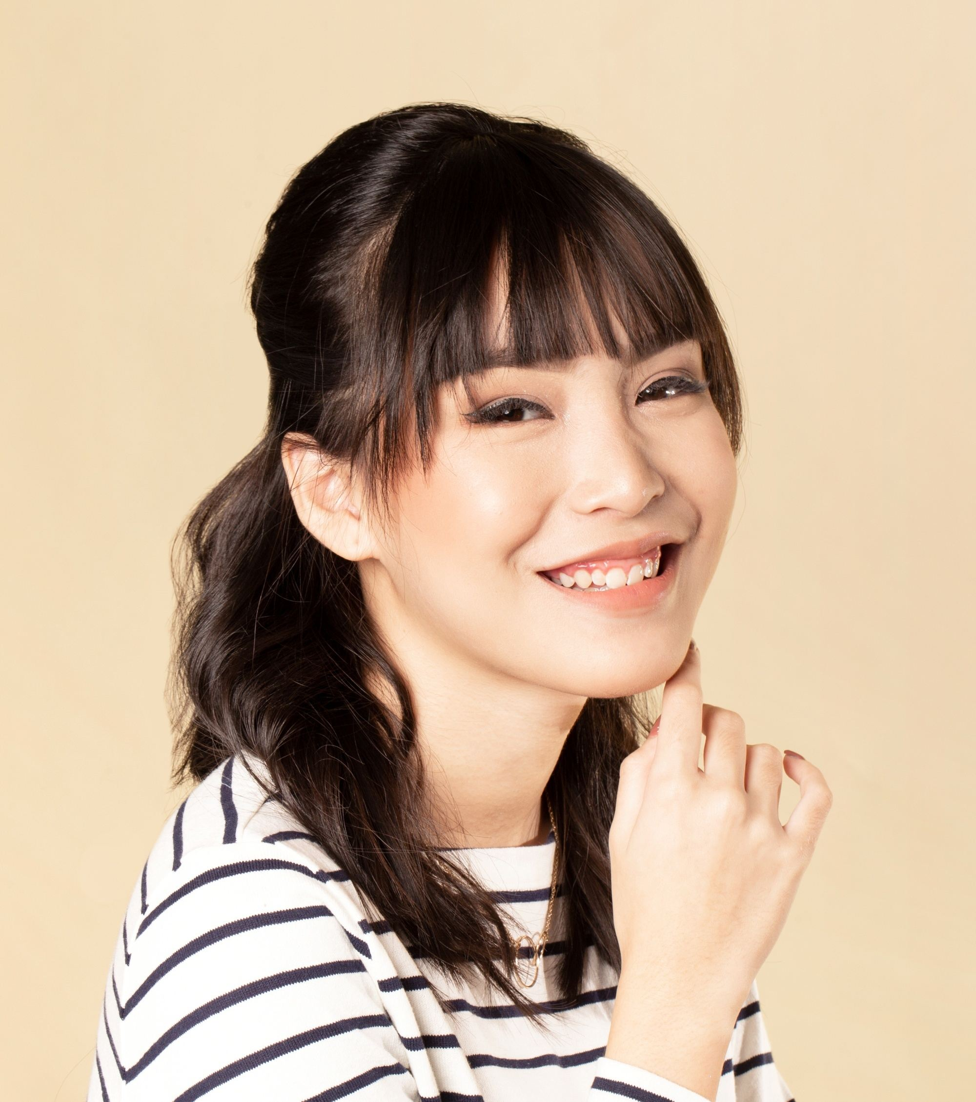 Asian woman with a half updo shoulder length hairstyle with bangs smiling