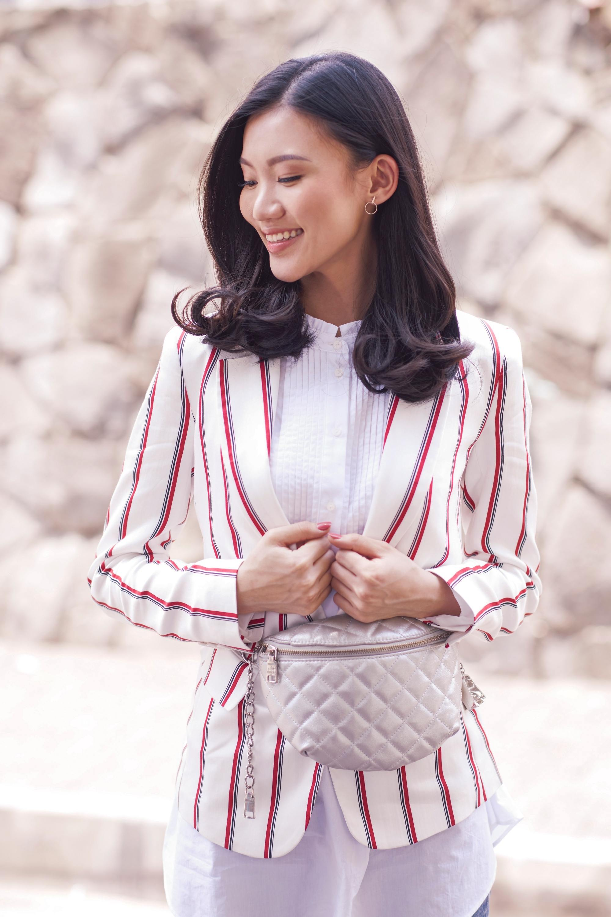 Asian woman with black blown out shoulder length hair wearing a striped suit