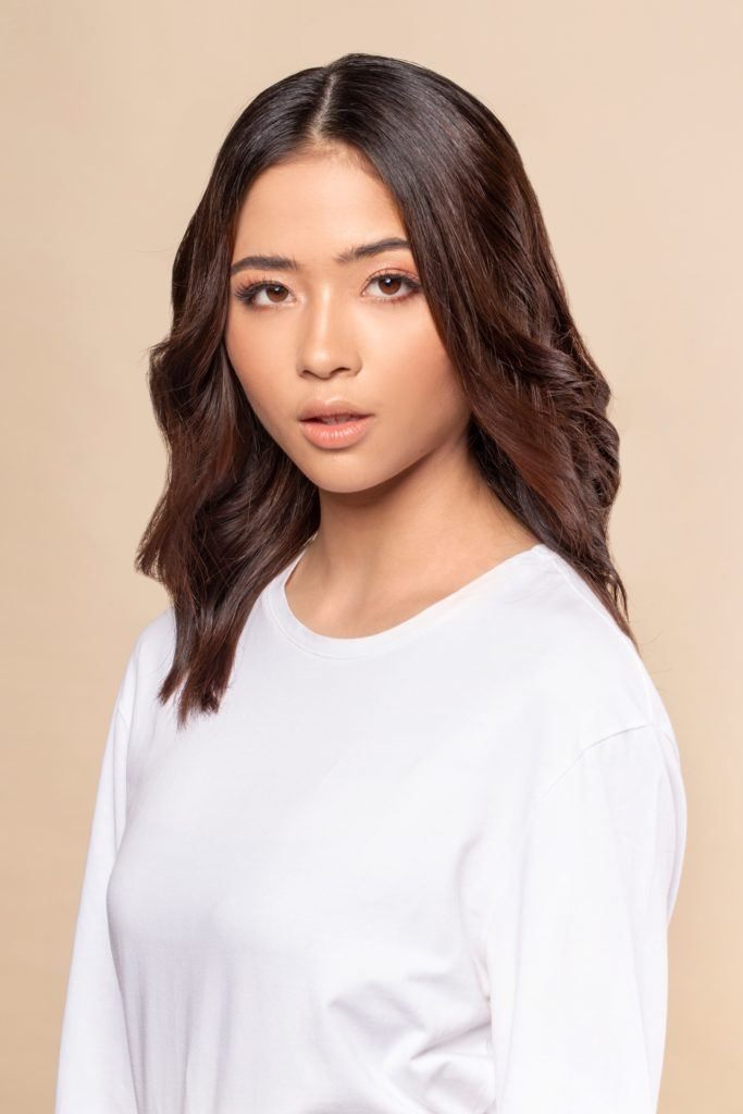 Space buns for short hair: Asian woman with shoulder-length dark brown hair wearing a white shirt