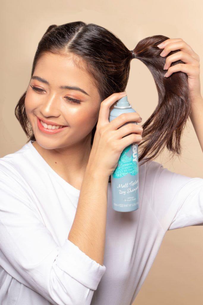 Space buns for short hair: Asian woman spraying dry shampoo on her dark brown hair