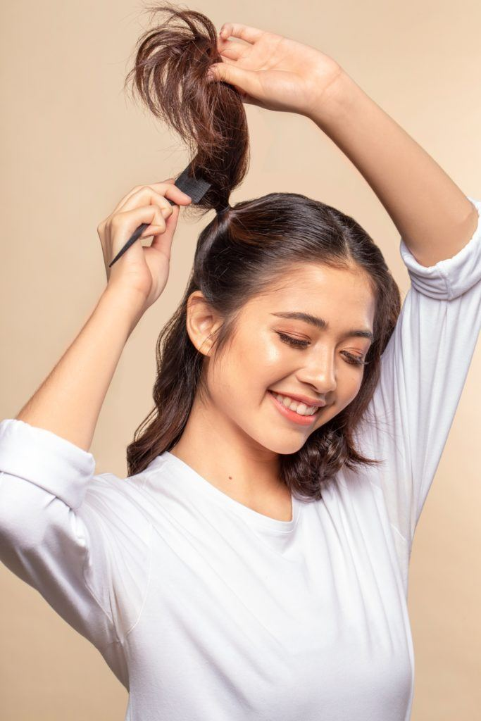 Space buns for short hair: Asian woman teasing her dark brown hair and smiling