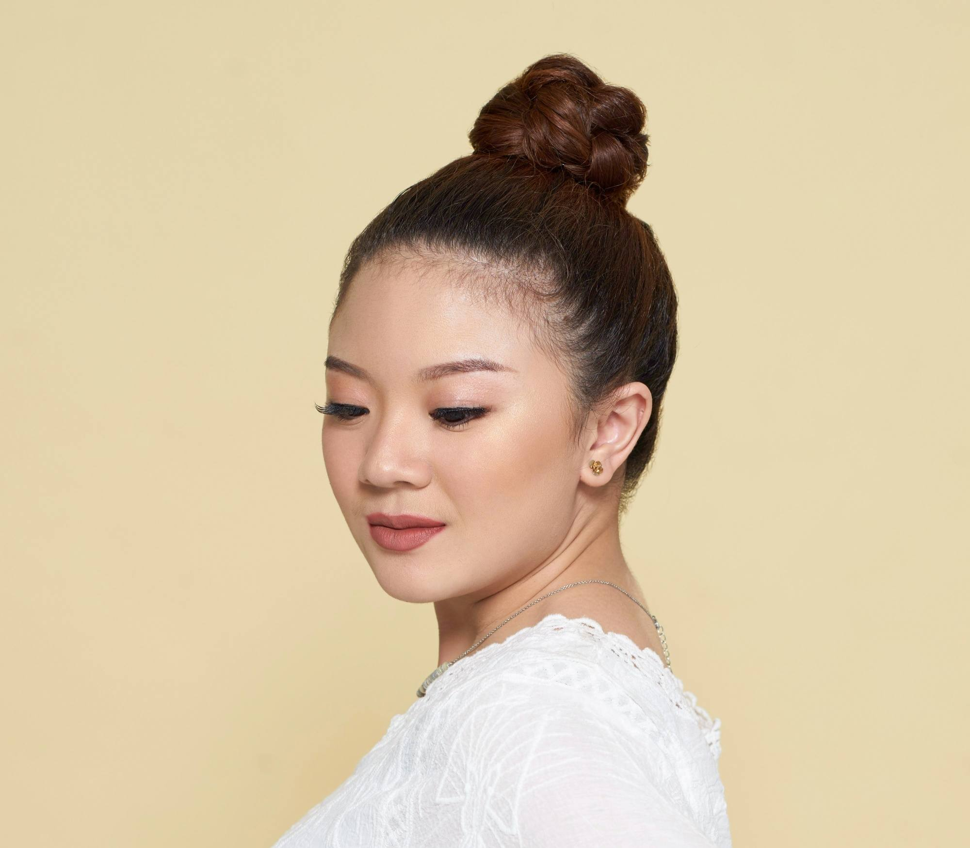 Summer Updos: Closeup shot of an Asian woman with dark hair in top knot