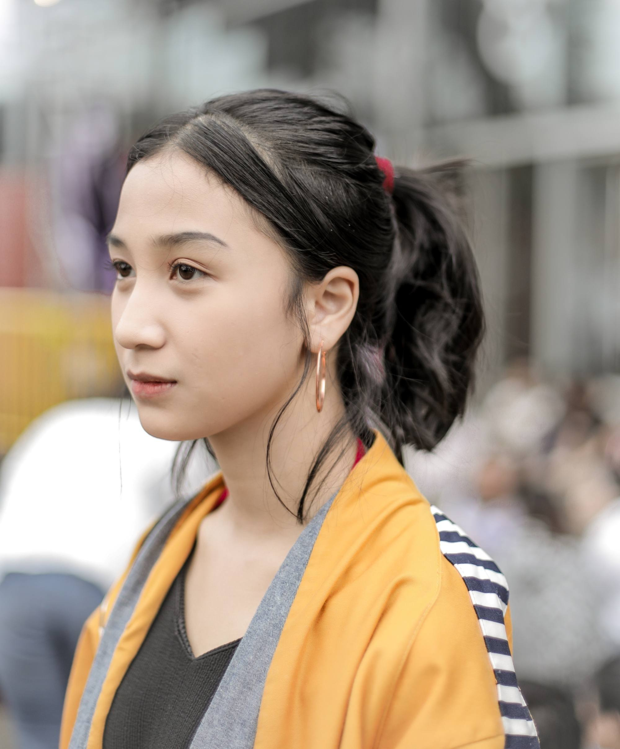 Summer updos: Closeup shot of an Asian woman with black wavy hair in a ponytail