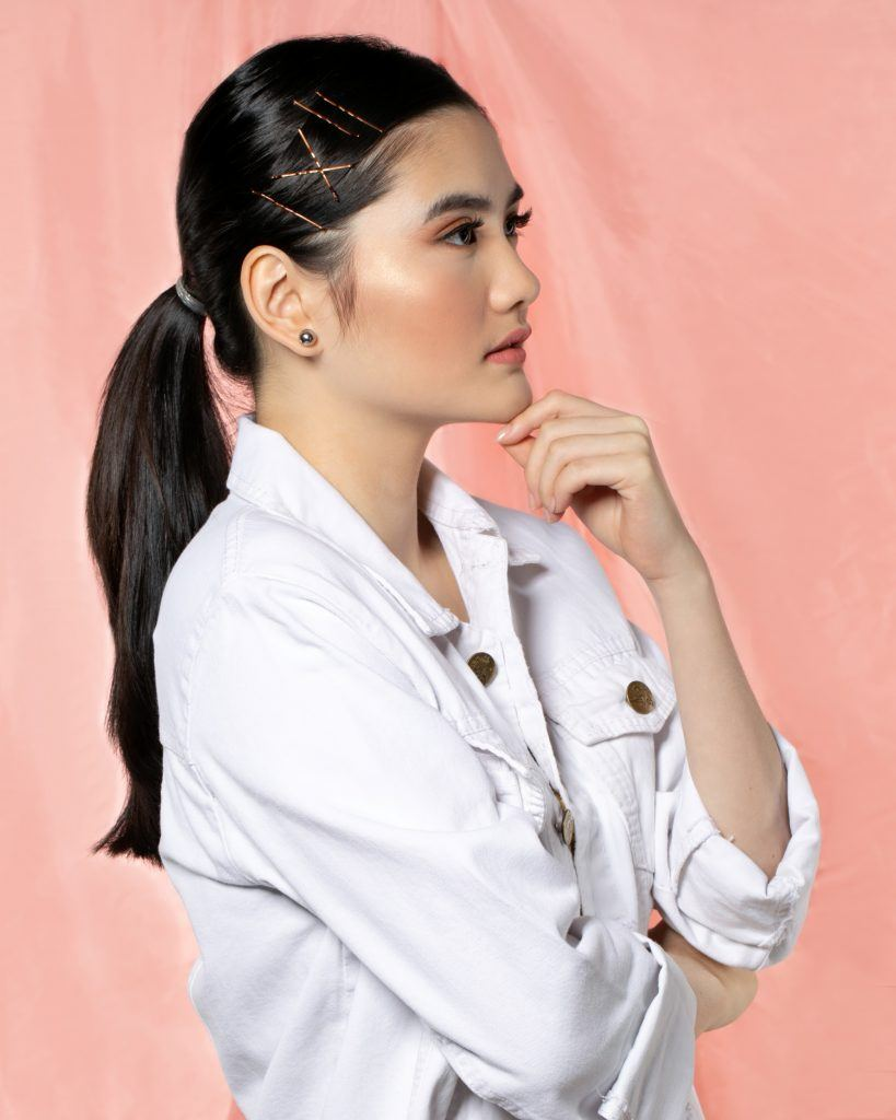 Asian woman with ponytail with bobby pins wearing a white jacket