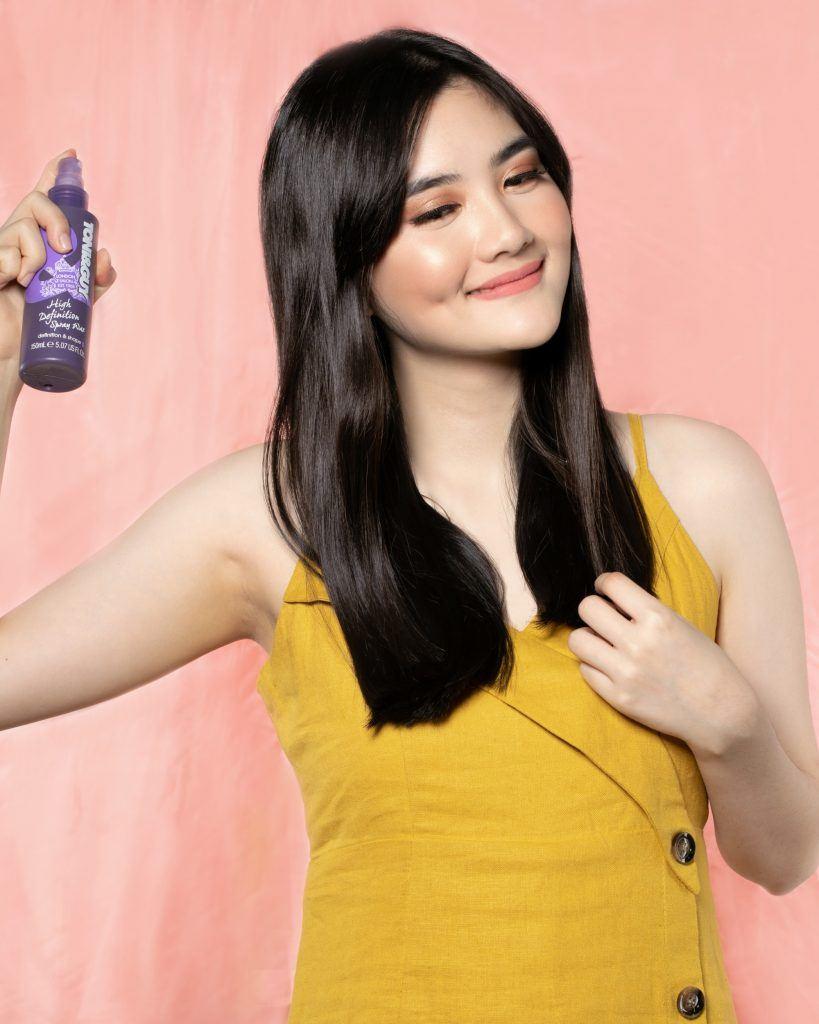 Asian woman spraying hair wax on her long black mane