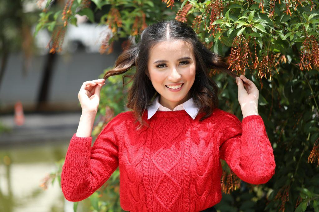 Asian woman with '90s half up pigtails wearing a red sweater outdoors