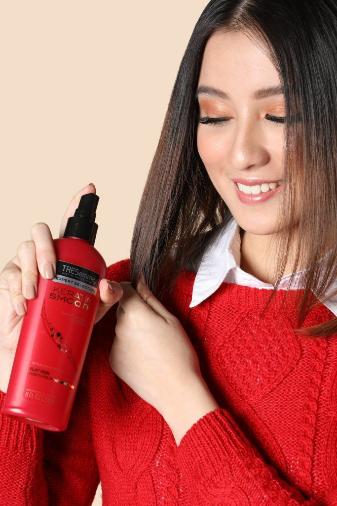 Asian girl wearing a red jacket is spraying heat protectant on her hair before creating her 90s half up pigtails