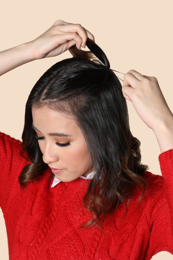 90s half up pigtails: Asian girl wearing a red jacket is tying her hair up for her '90s half up pigtails
