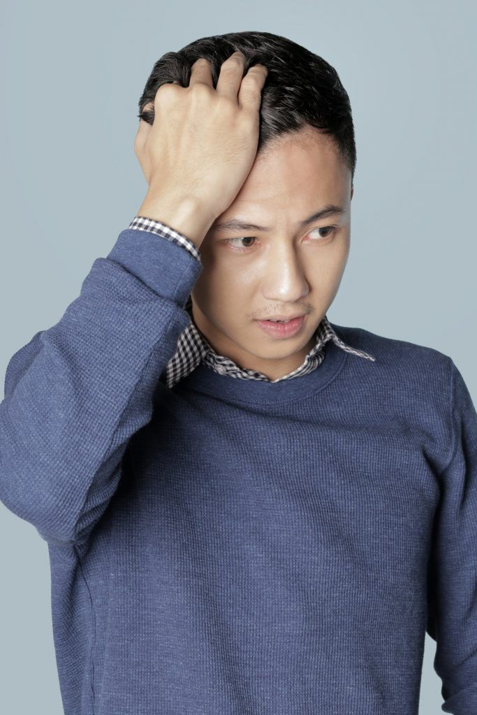 Easy Comb Over Hairstyle for Men: Asian man applying putty on his hair
